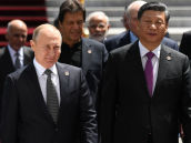 Russian President Vladimir Putin and Chinese President Xi Jinping, right, arrive for posing for a family photo during the Shanghai Cooperation Organization (SCO) summit, in Bishkek, Kyrgyzstan
